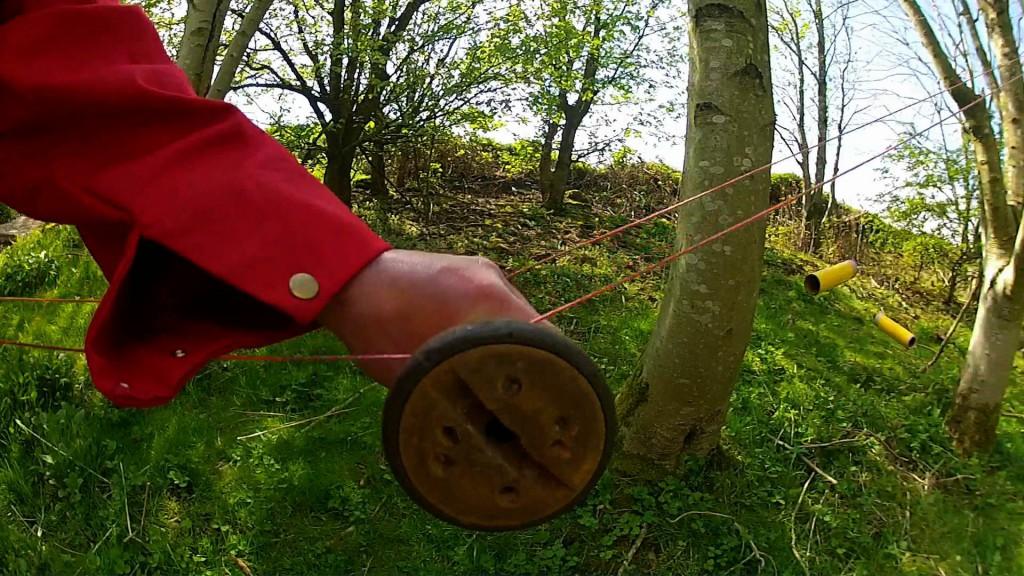 bobbin on pair of string rails in hand