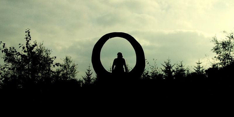 woman eclipsed by circular sculpture